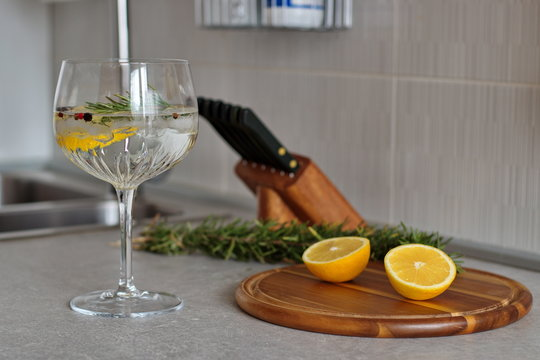 Preparing gin and tonic with lemon and rosemary in crystal glass on kitchen desk