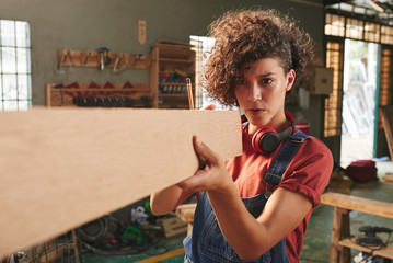Young concentrated woman with curly hair holding wooden plank and measuring its length with her eyes