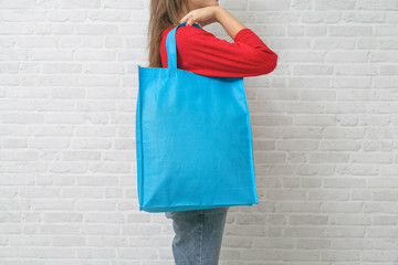 Womenl is holding bag canvas fabric for mockup blank template.
