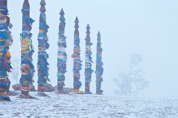 Lake Baikal in snowfall and bad weather. Olkhon Islands, Cape Burhan. Totem poles with colored ribbons and flags in the snow and fog