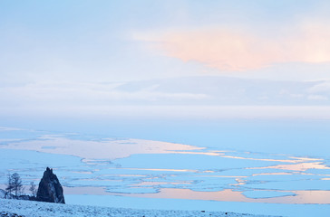 Baikal Lake in spring bad weather. View from Olkhon Island to snowfall over the Small Sea Strait during the spring ice drift. Seaside Ridge in fog. Pink clouds at sunset. Minimalist landscape