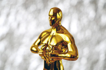 Hollywood Golden Oscar Academy award statue on silver background. Success and victory concept.