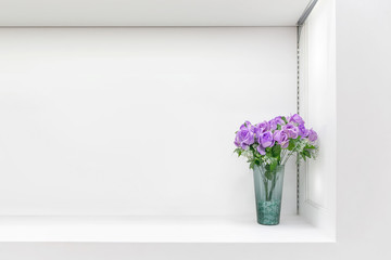 White shelf against white wall with a pot.