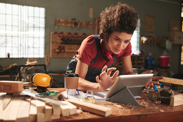 Young pretty woman with curly hair watching woodworking tutorial on digital tablet while leaning on messy table covered with sawdust