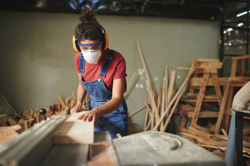 Professional female carpenter in protective eyewear, earmuffs and mask cutting wooden board on table saw Wall mural
