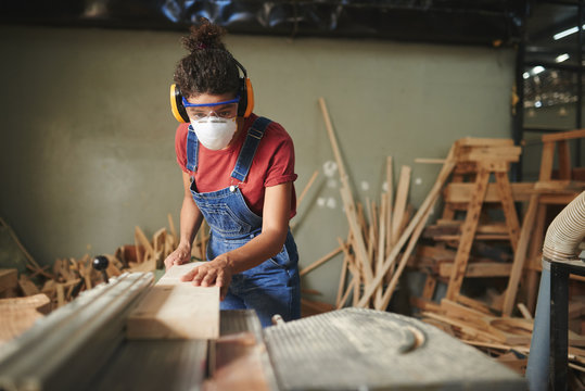 Professional female carpenter in protective eyewear, earmuffs and mask cutting wooden board on table saw