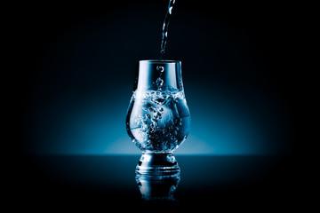 Liquid splashing into a glass - blue toned & isolated on black