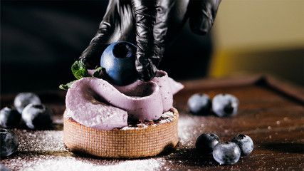 Pastry chef is puts a berry on top of cake, close-up. Professional baker is making blueberry cake in commercial bakery