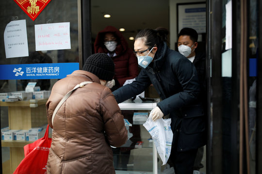 Staff members with face masks and protective glasses attend to a customer at a pharmacy as the country is hit by an outbreak of the new coronavirus, in Beijing
