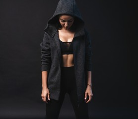 Image of young female model in sportswear standing on black background with copyspace