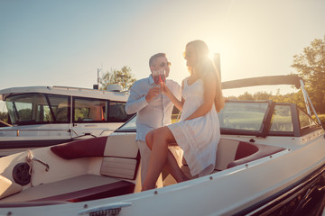Couple in a river boat or yacht toasting with sparkling wine