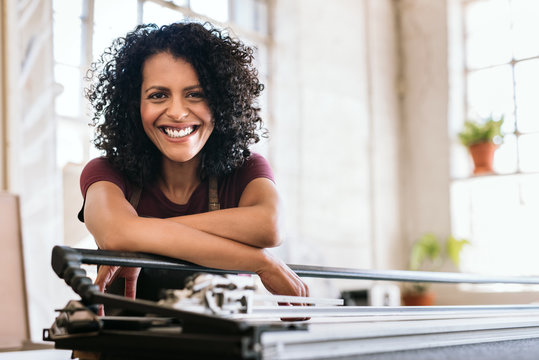 Smiling young woman leaning on a workbench in her studio