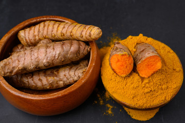 A wooden bowl with a halved fresh turmeric root and dried curcuma powder and a wooden bowl with fresh whole turmeric roots on a black slate plate background.