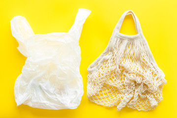 Zero waste concept. Textile and plastic bag on yellow background top-down