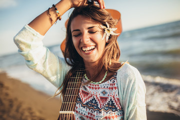 Smiling girl walking on the beach holding a guitar in her hands.