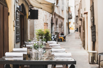 Foto auf AluDibond Altes Gebaude Outdoor restaurant in Italy. Empty glasses set in cafe with beautiful italian street at the background. Food, travel and vacation concept
