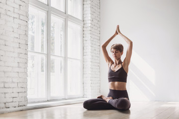 Young beautiful woman practicing yoga near floor window in yoga studio. Young beautiful girl doing exercises at home. Harmony, balance, meditation, relaxation, healthy lifestyle concept