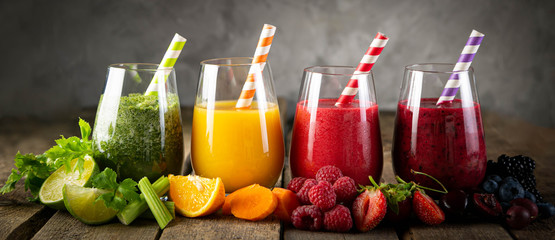 Poster Juice Selection of colorful smoothies and ingredients in glasses, rustic background
