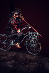 Old witch riding a retro bicycle
