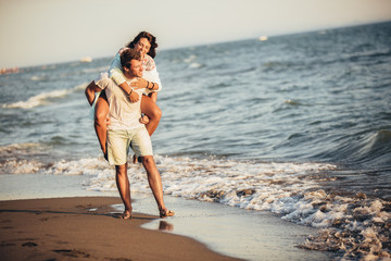 Handsome young man giving piggyback ride to girlfriend on beach. Young couple enjoying summer...