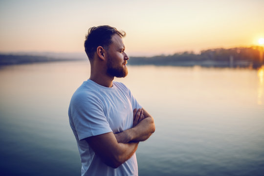 Handsome bearded blond caucasian man standing on cliff with arms crossed and looking at beautiful sunset. In background is river.
