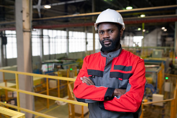 Portrait of serious confident young Afro-American factory worker in hardhat and protective suit standing in industrial shop