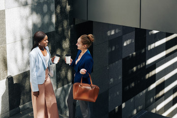 Smiling businesswomen standing on stairs outdoors with take out coffee and gossiping about work