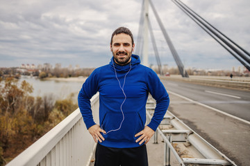 Attractive smiling young sportsman standing on the bridge and holding hands on hips. In ears are earphones. Outdoor fitness on cloudy weather concept. Urban exterior.