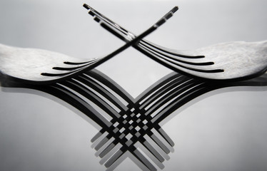 Two fork cross each other with reflection shadow of fork pattern with grey background