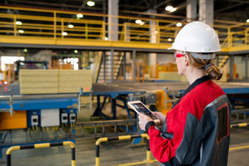 Rear view of busy woman in hardhat and safety goggles using tablet while controlling production...