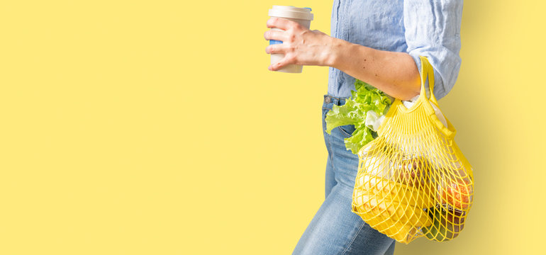 Zero waste shopping - female holding yellow reusable shopping bag and coffee mug on bright background, copy space
