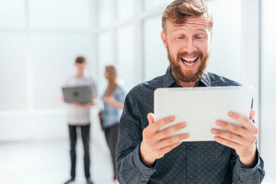 surprised businessman reading SMS on his tablet