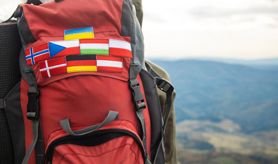 travel life style passion concept picture of backpack with country flags stripes of Ukraine, Germany, Austria, Denmark, Norway, Hungary and Czech Republic blurred background mountains highland view
