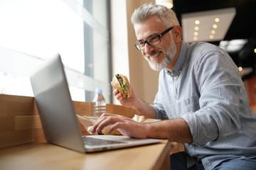 Man having lunch in front of laptop Fototapete
