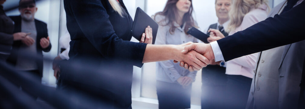 business people shaking hands while standing near an office window