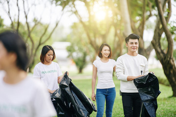 Group of young smiling Asian volunteers collecting garbage in city park