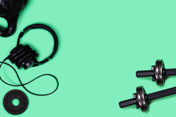 Sports picture. Kettlebells and dumbbells on mint green background. Flat lay, top view, copy space.