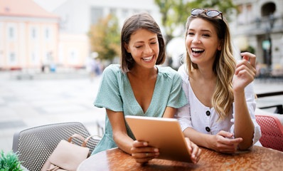 Holidays, tourism, technology friends concept. Beautiful women with tablet in cafe outside