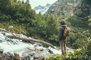 Man traveler alone with backpack looking at mountain river among green woods.