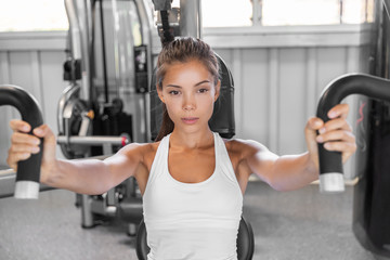 Gym workout Asian woman focused and motivated training on pec deck chest press fly machine. Fitness workout.