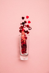 Valentine's day shots. Shot glass with heart confetti on pastel pink background