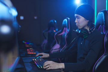 Side view portrait of young Asian man playing videogames in dark cyber like interior, copy space