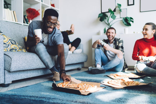 Multiracial friends eating pizza at home