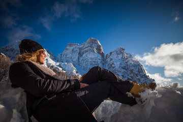 Blond girl lying on the snow looking at the snowy Mount Pelmo, Dolomites, Italy. Concept: happiness in the snow, happy people surrounded by nature, happy people on vacation