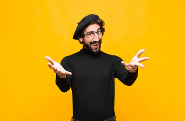 young french artist man feeling happy, astonished, lucky and surprised, like saying omg seriously? Unbelievable against orange wall