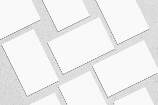 Closeup of empty white rectangle business card mockups lying diagonally on neutral grey concrete background. Flat lay, top view. Open composition. Blank Template for Corporate Identity. Copy space