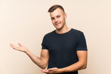 Young handsome blonde man over isolated background extending hands to the side for inviting to come