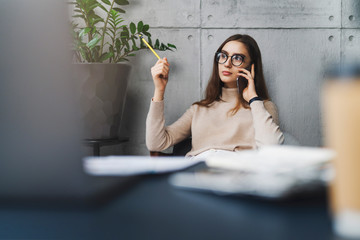 Young female professional sitting at office desk and talking to customer on mobile phone. Digital tools and mobile solutions for corporate cllients. Free phone and video calls using online messengers.