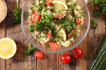 Fotobehang - tabbouleh- semolina, tomato, cucumber and parsley on wood background