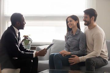 Caucasian couple listens African ethnicity realtor people discussing future deal